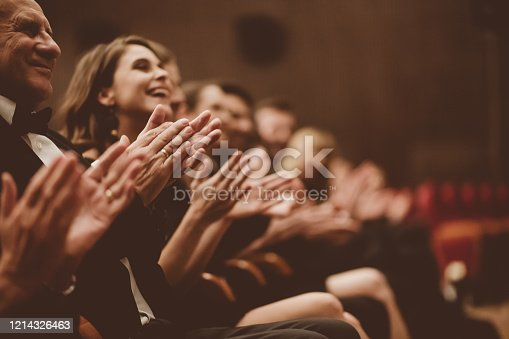 Side view of smiling spectators clapping hands in opera house. Men and women are watching theatrical performance. They are in elegant wear.
