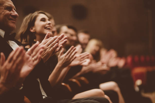 Excited audience clapping in the theater stock photo