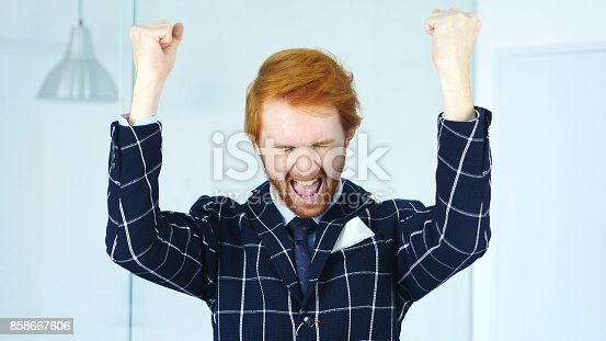888751614 istock photo Excited Beard Man Celebrating Success in His Office 858667606