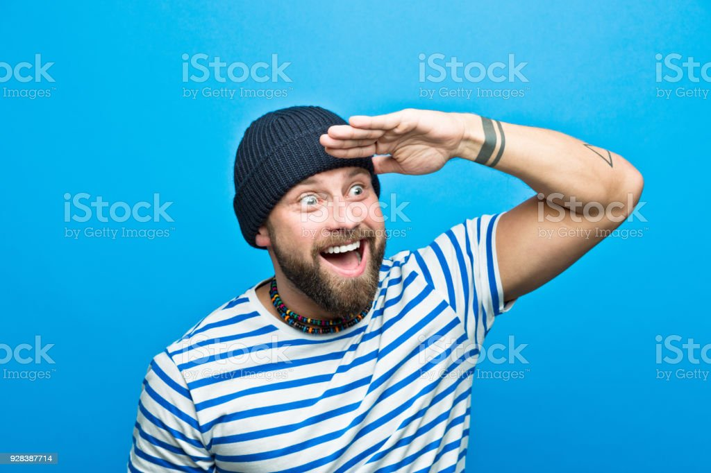 Excited bearded sailor looking away with raised hand Portrait of happy, surprised bearded man wearing striped t-shirt and beanie hat looking away with raised hand. Studio shot, blue background. 30-34 Years Stock Photo