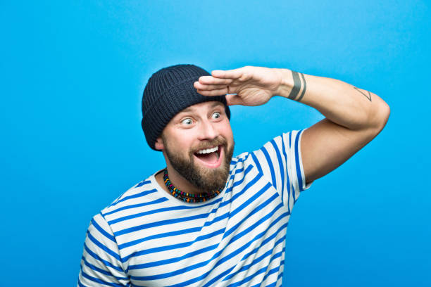 Excited bearded sailor looking away with raised hand Portrait of happy, surprised bearded man wearing striped t-shirt and beanie hat looking away with raised hand. Studio shot, blue background. sailor stock pictures, royalty-free photos & images