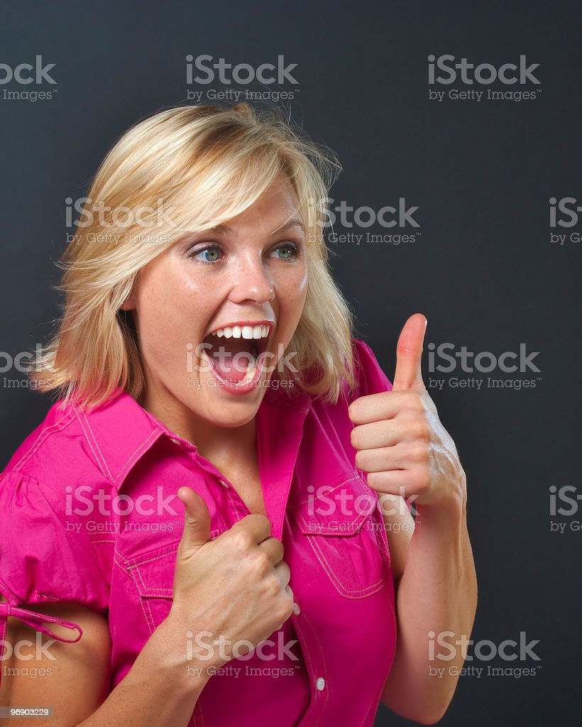 Excited  beautiful blonde woman in pink giving thumbs up sign royalty-free stock photo