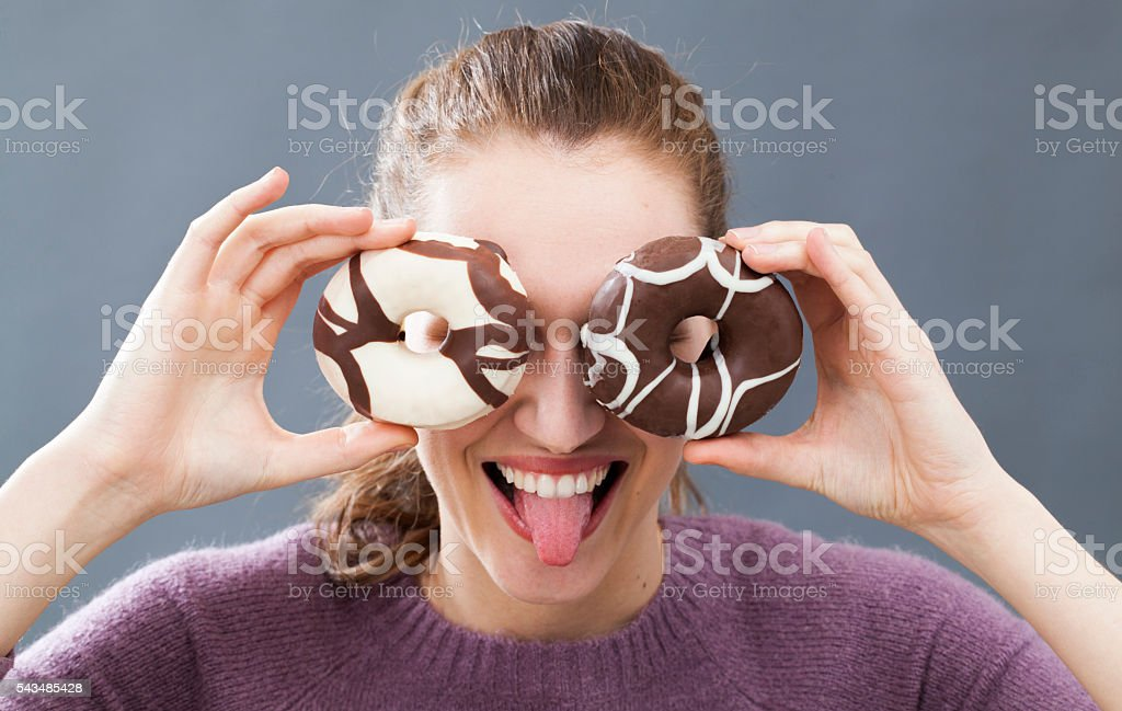 excited beautiful girl holding donuts on her eyes for joke stock photo