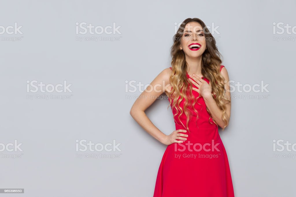 Excited Beautiful Woman In Red Dress Is Holding Hand On Chest And Laughing zbiór zdjęć royalty-free