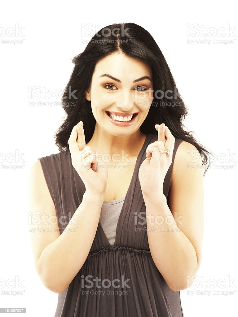 Excited beautiful young woman with fingers crossed royalty-free stock photo