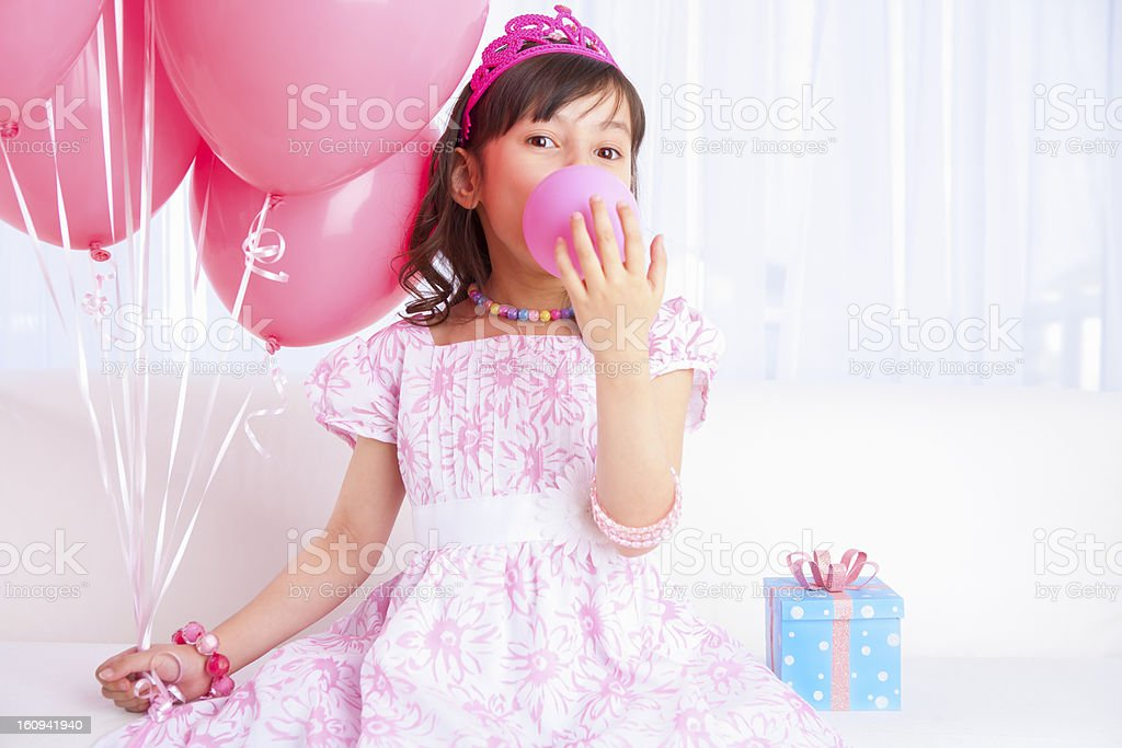Excited birthday girl blowing a balloon royalty-free stock photo