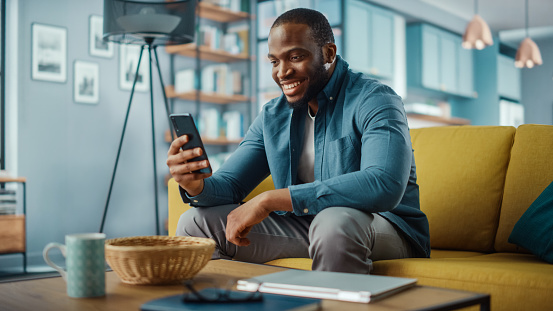 Excited Black African American Man Having a Video Call on Smartphone while Sitting on a Sofa in Living Room. Happy Man Smiling at Home and Talking to His Friends and Family Over the Internet.