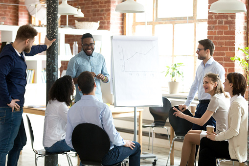 Excited black coach make flipchart presentation for employees