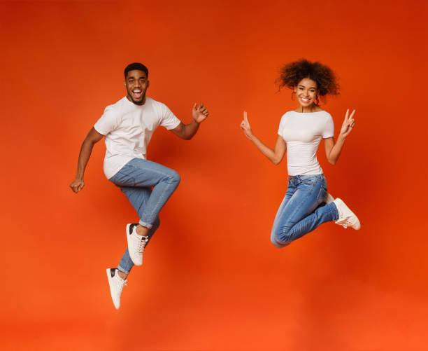 excited black couple jumping on orange background - figura femminile foto e immagini stock