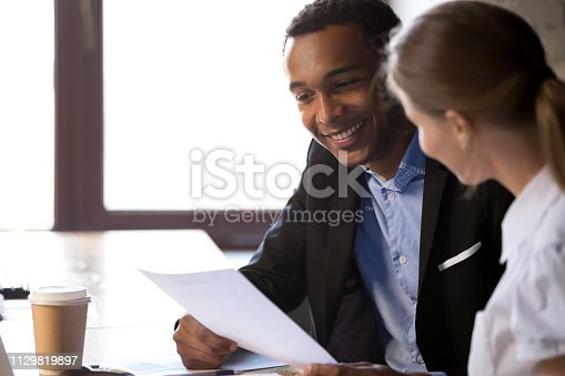 istock Excited black employer read applicant resume at interview 1129819897