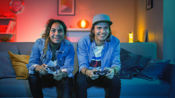 excited black gamer girl and young man sitting on a couch and playing video games on console. they plays with wireless controllers. cozy room is lit with warm and neon light. - man joystick imagens e fotografias de stock