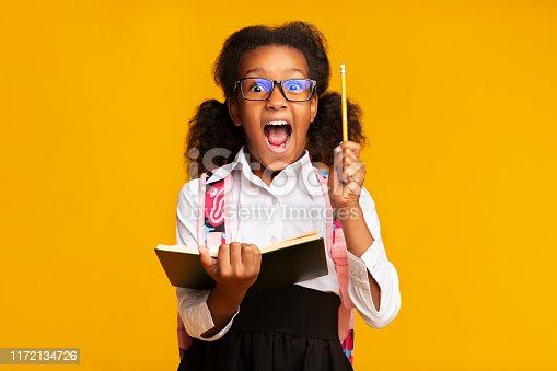 1176772377 istock photo Excited Black Schoolgirl Holding Book And Pencil Over Yellow Background 1172134726