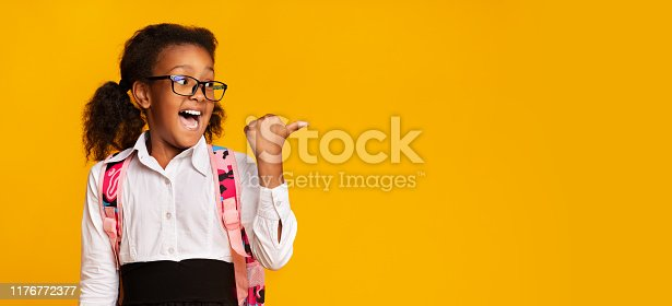 istock Excited Black Schoolgirl Pointing Thumbs At Copy Space In Studio 1176772377