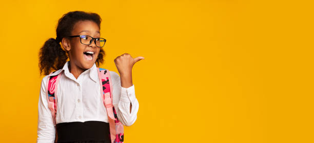 Excited Black Schoolgirl Pointing Thumbs At Copy Space In Studio School Offer. Excited Black First-Grade Schoolgirl Pointing Thumbs At Copy Space On Yellow Background In Studio. Panorama nerd hairstyles for girls stock pictures, royalty-free photos & images