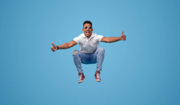 Excited black student jumping and gesturing thumbs up stock photo