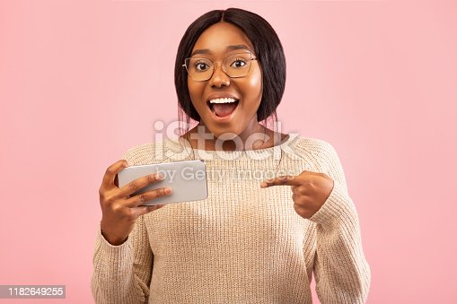 1132512759istockphoto Excited Black Woman Pointing Finger At Cellphone Standing, Pink Background 1182649255