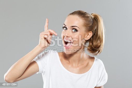 istock Excited blond hair young woman pointing 481811394