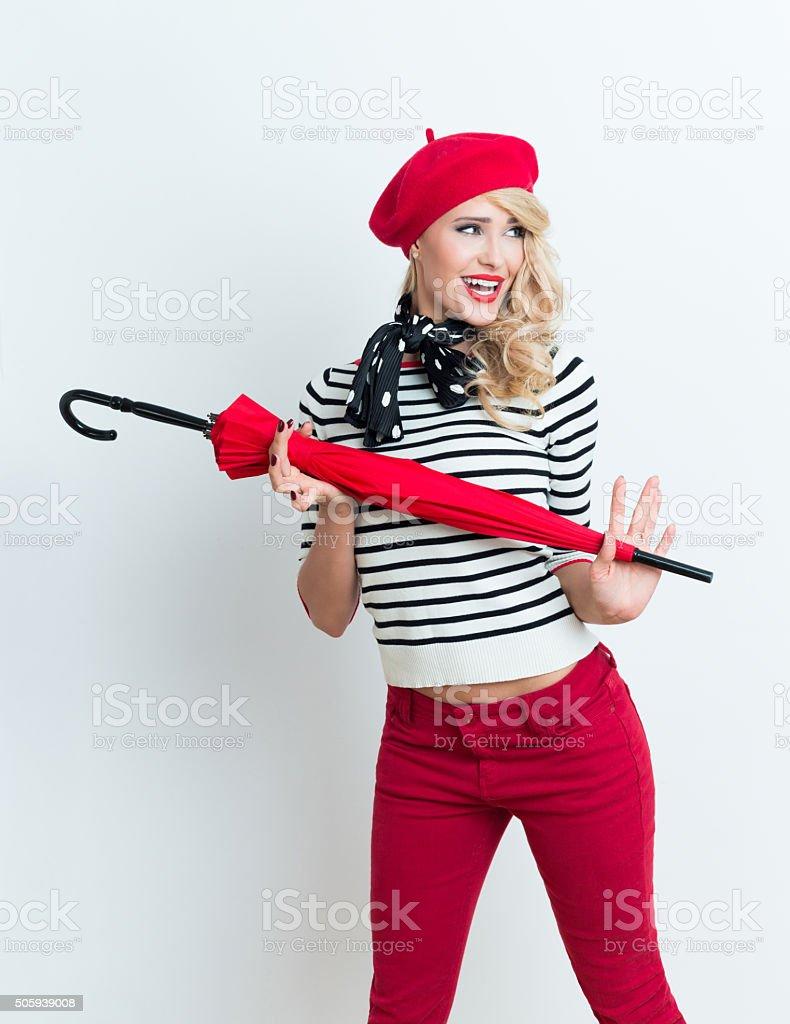 Excited blonde french woman wearing red beret, holding an umbrella Portrait of excited beautiful blonde woman in french outfit, wearing a red beret, striped blouse and neckerchief, holding a red umbrella. Adult Stock Photo