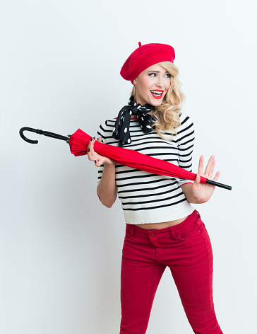 Excited Blonde French Woman Wearing Red Beret Holding An Umbrella Stock Photo - Download Image Now