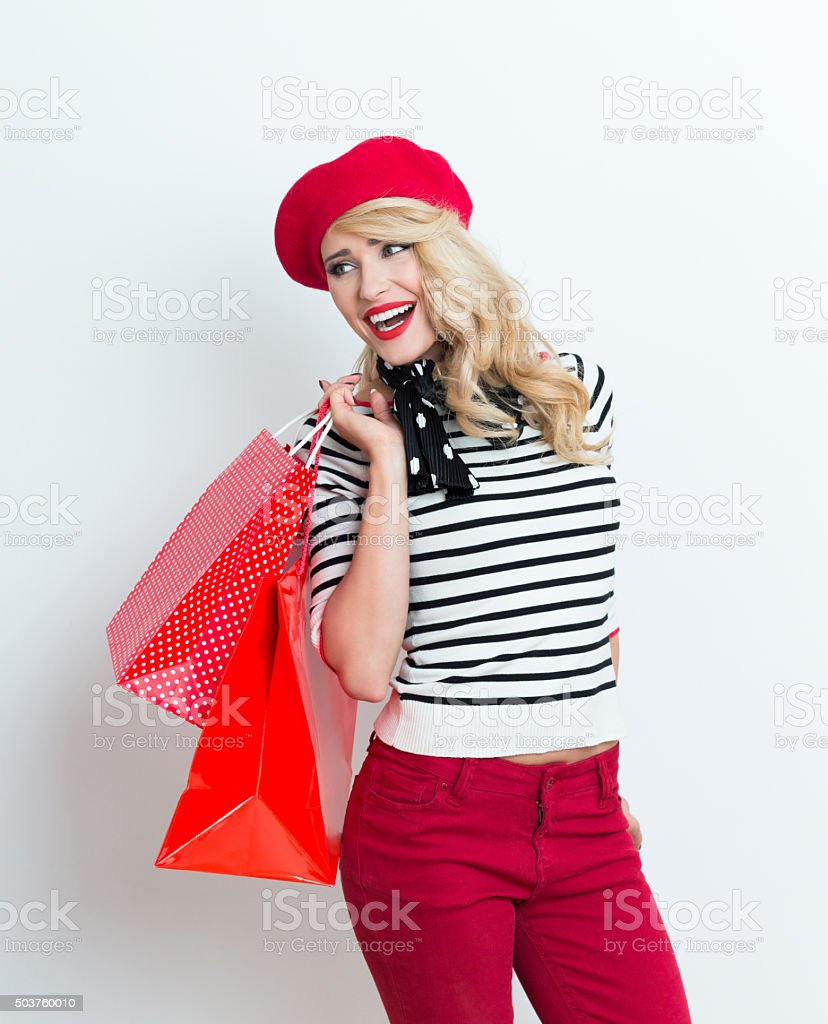 Excited blonde french woman wearing red beret, holding shopping bags Portrait of sensual beautiful blonde woman in french outfit, wearing a red beret, striped blouse and neckerchief, holding shopping bags. Adult Stock Photo