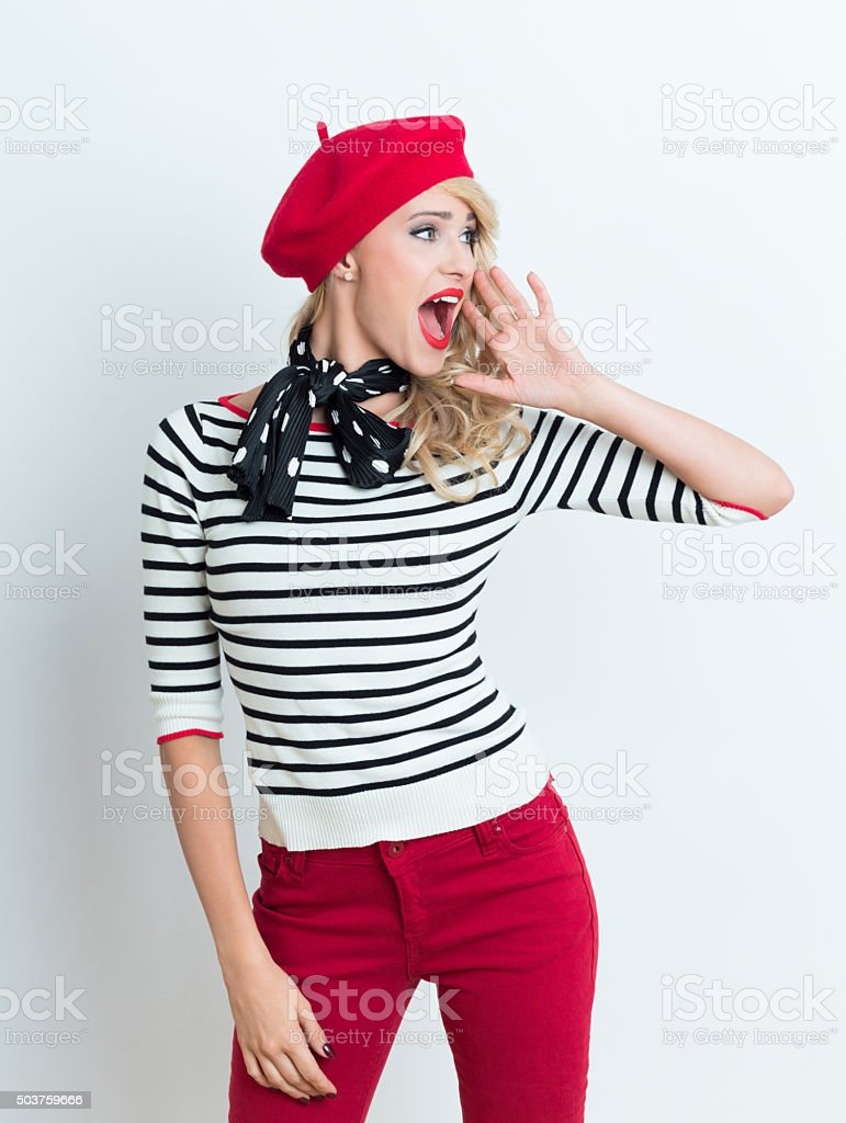 Excited blonde french woman wearing red beret Portrait of excited beautiful blonde woman in french outfit, wearing a red beret, striped blouse and neckerchief, looking away and shouting. Adult Stock Photo