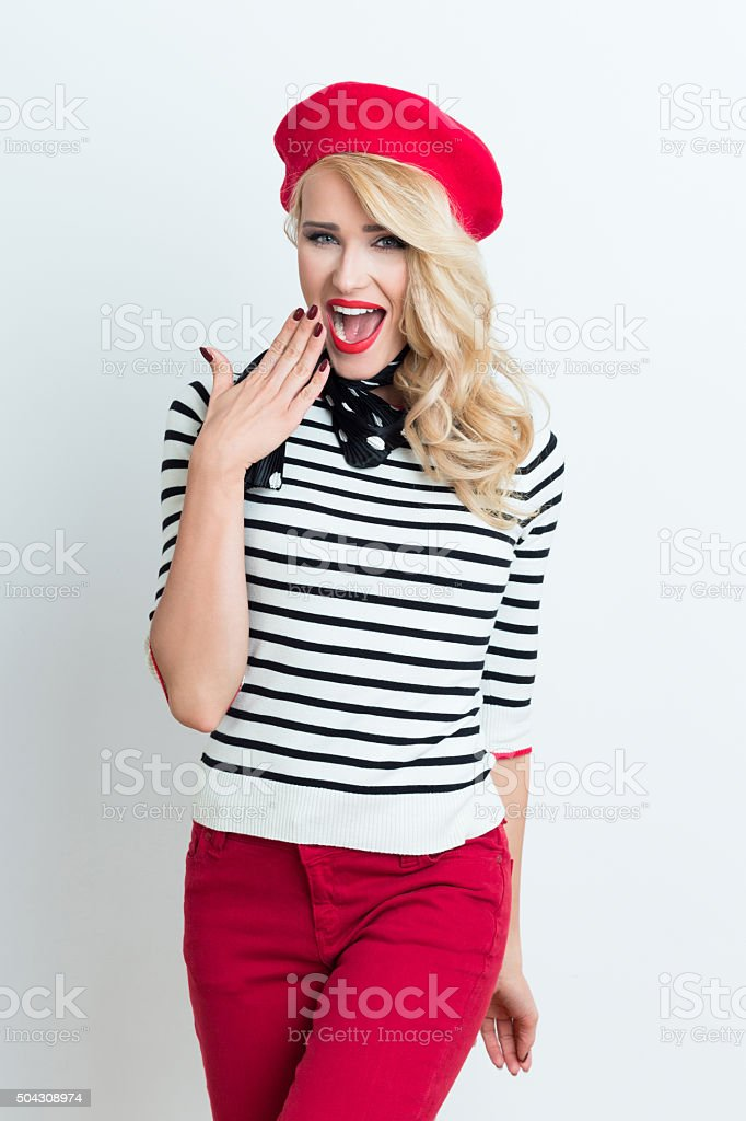 Excited blonde french woman wearing red beret Portrait of beautiful blonde woman in french outfit, wearing a red beret, striped blouse and neckerchief, laughing at camera. Adult Stock Photo