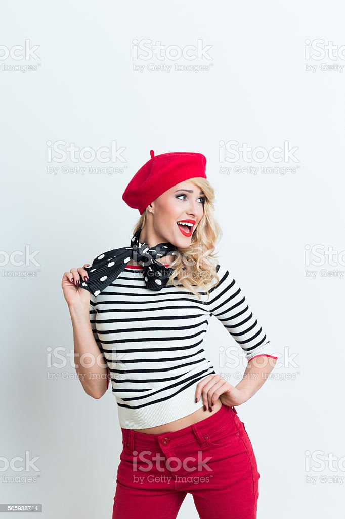 Excited blonde french woman wearing red beret Portrait of excited beautiful blonde woman in french outfit, wearing a red beret, striped blouse and neckerchief, looking away with mouth open. Adult Stock Photo