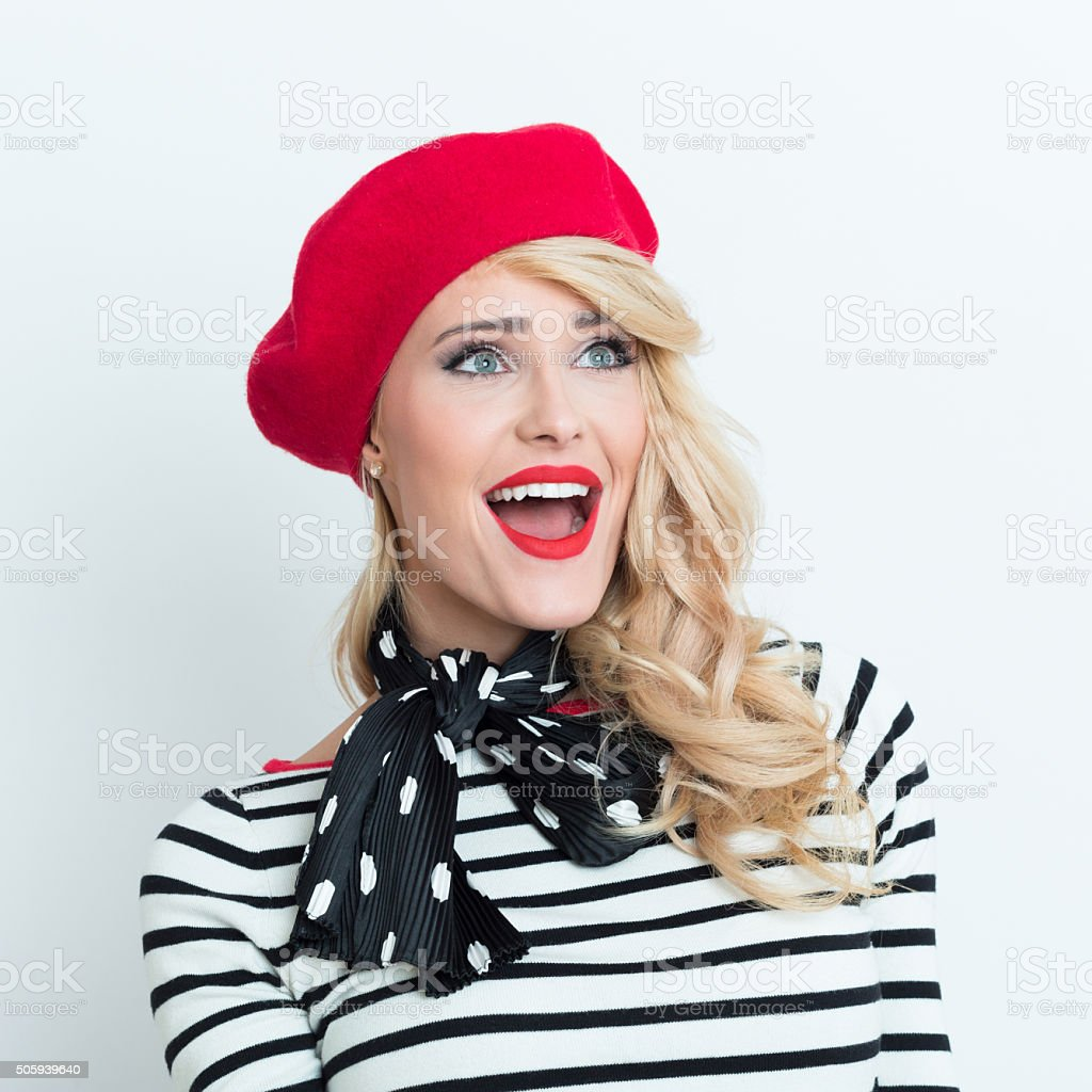 Excited blonde french woman wearing red beret Portrait of excited beautiful blonde woman in french outfit, wearing a red beret, striped blouse and neckerchief, laughing away with mouth open. Adult Stock Photo