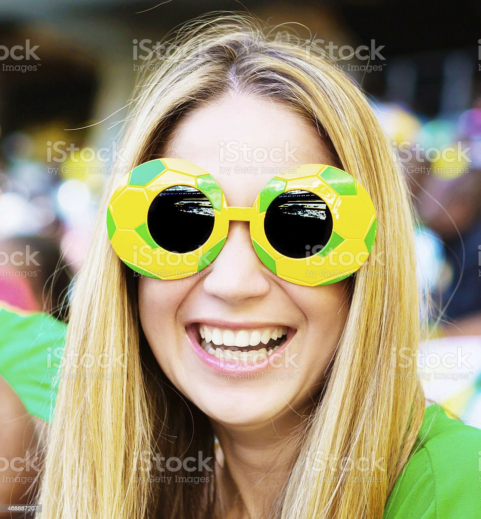 Excited blonde soccer fan in funky sunglasses at football match stock photo