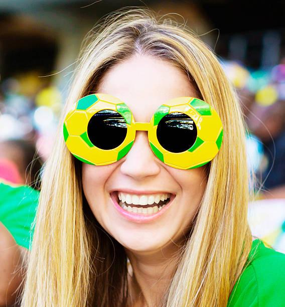 glücklich blonde fußball-fan in funky sonnenbrille im fußball - spielerfrauen stock-fotos und bilder
