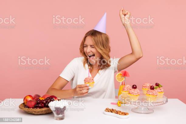Photo of Excited blonde young adult female celebrating birthday, holding cake with candle, yelling happily, enjoying dream come true on her holiday.
