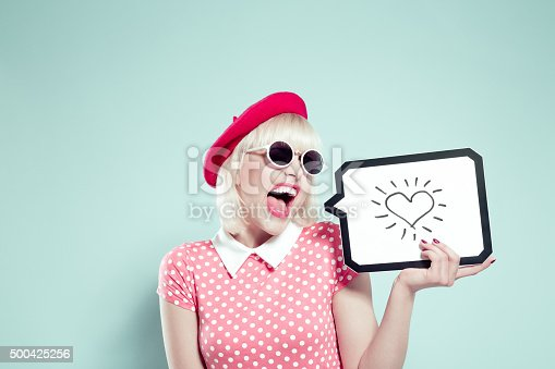 Portrait of excited blonde young woman wearing pink dotted dress, red beret and sunglasses, holding speech bubble with drawn heart. Studio shot, one person, turquoise background.