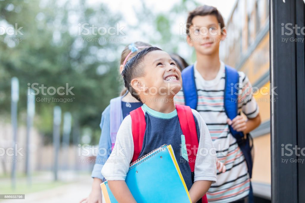Excited boy can't wait to get on a school bus stock photo