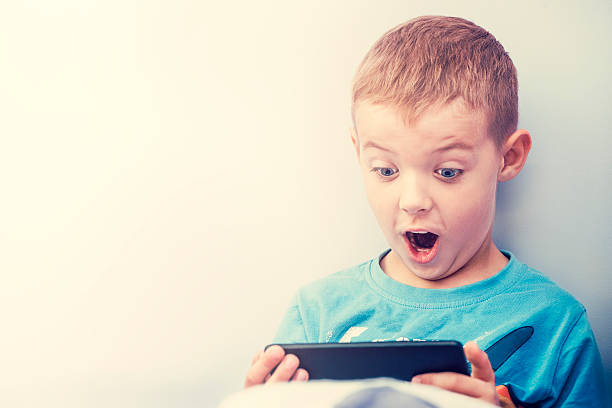 excited boy playing with a smartphone. - smartphone addiction not groups stock pictures, royalty-free photos & images