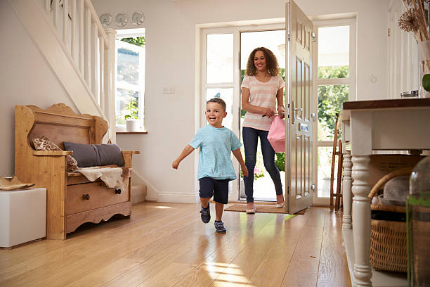 excited boy returning home from school with mother - arrival stock photos and pictures