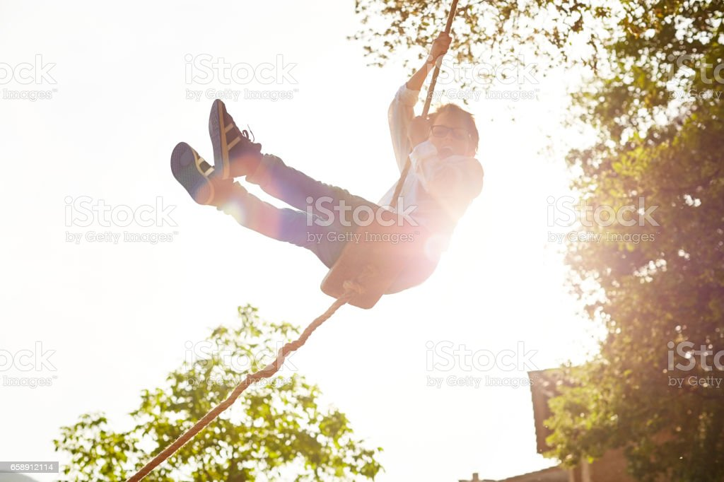 Excited boy swinging at back yard on sunny day stock photo