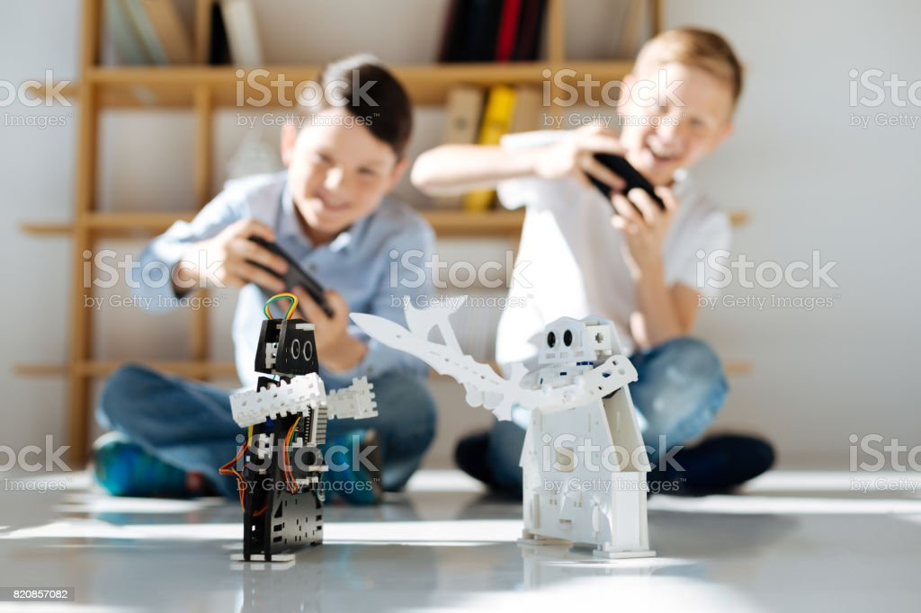 Excited boys organizing battles of robotic warriors stock photo
