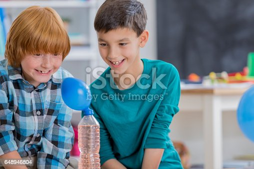 648947070istockphoto Excited boys watch chemical reaction during science experiment 648946804