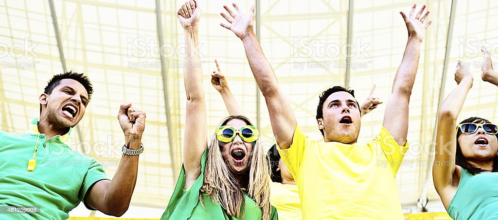 Excited Brazilian soccer supporters cheer their team at stadium stock photo