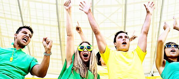 glücklich brasilianischen fußball-fans feuern sie ihr team im stadion - spielerfrauen stock-fotos und bilder
