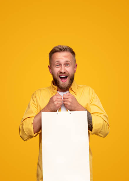 Excited bright man with blank paper bag stock photo