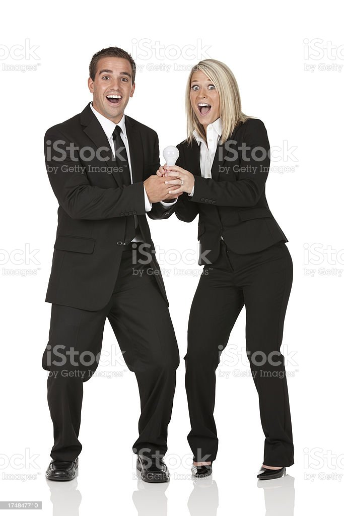 Excited business couple holding a light bulb royalty-free stock photo