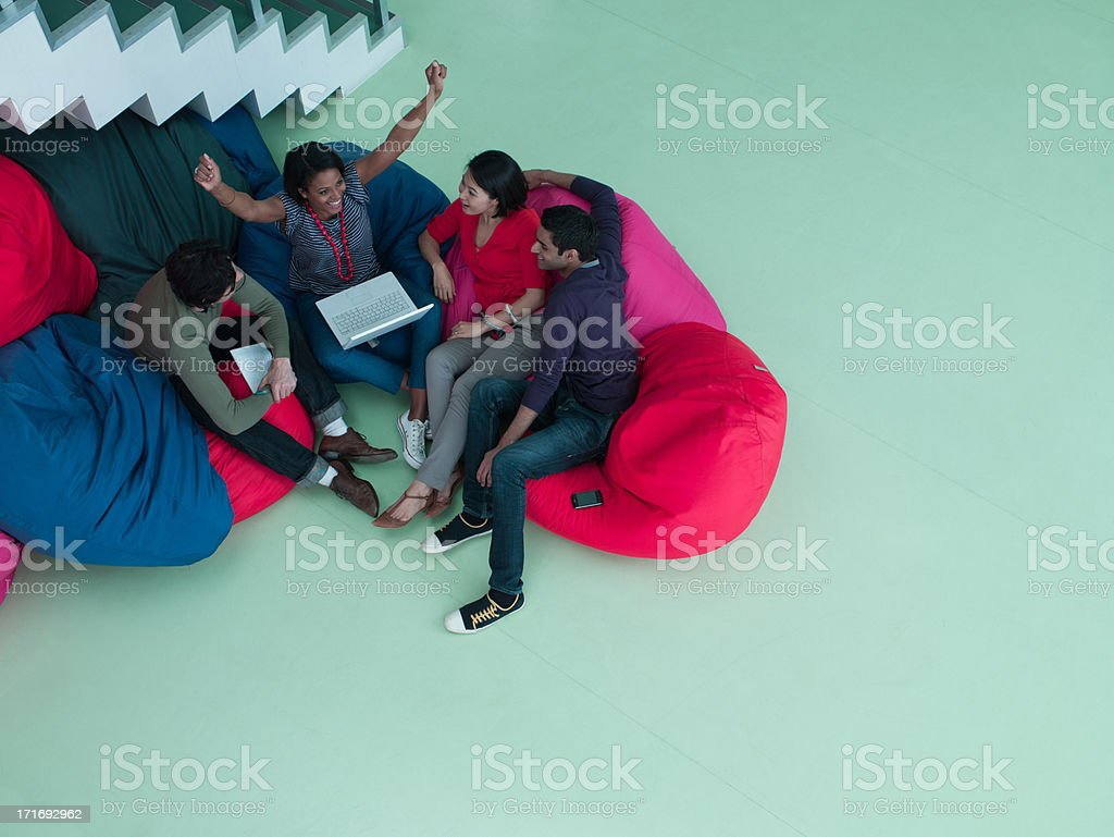 Excited business people with arms raised sitting in bean bag chairs and looking at laptop stock photo
