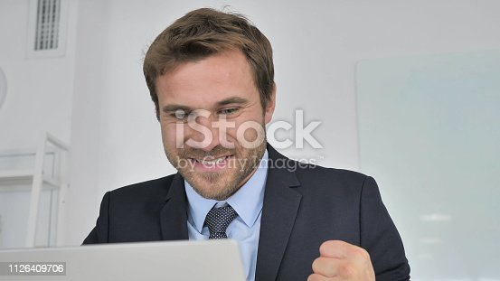 888751614 istock photo Excited Businessman Celebrating Success at Work 1126409706