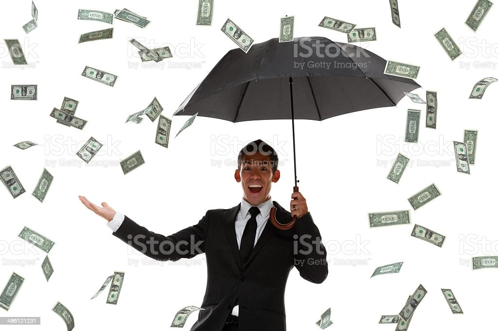 Excited businessman holding hand out in a money rain storm stock photo