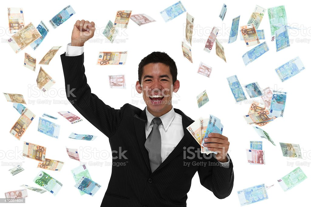 Excited businessman in a money rain storm stock photo