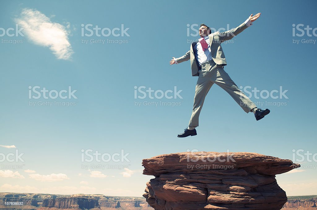 Excited Businessman Jumping Sky Mesa Rock with Canyon Background stock photo