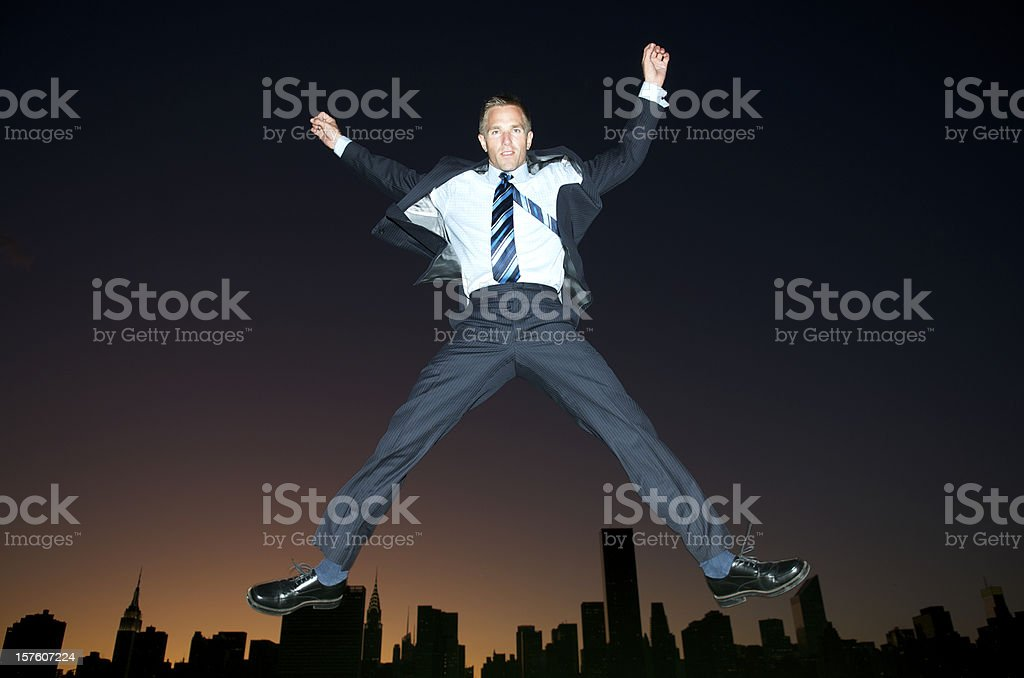 Excited Businessman Jumping Sunset City Skyline stock photo