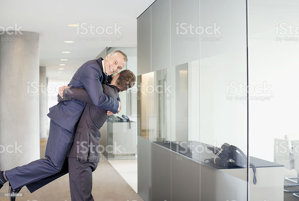 Excited businessman lifting co-worker in office corridor stock photo