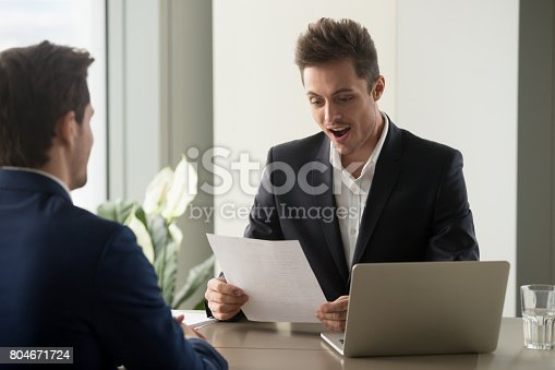 istock Excited businessman looking amazed while reading document, impressed by resume 804671724
